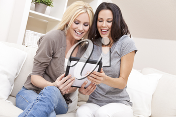 Overhead photograph of two beautiful young women at home sitting on sofa or settee using a tablet PC computer and laughing
