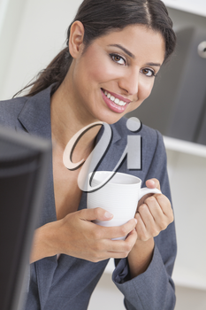 Beautiful young Latina Hispanic woman or businesswoman in smart business suit sitting at a desk drinking coffee in an office
