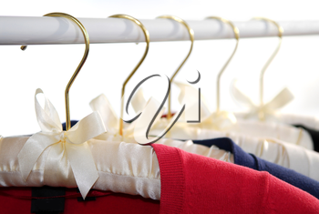 Colorful women's sweaters on a rack on padded hangers