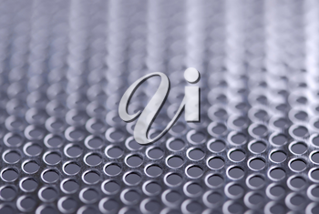 Abstract background of perforated metal with very shallow dof