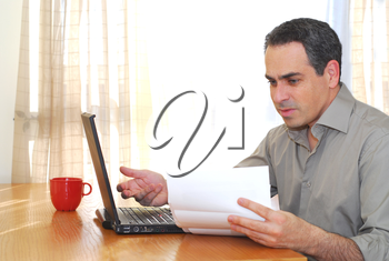 Man sitting at his desk with a laptop looking at bills