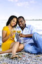 Young romantic couple celebrating with wine at the beach