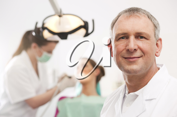 Dentist in his surgery looking at the viewer, in the background his assistant is giving a female patient a treatment