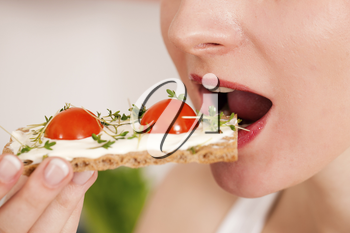 Woman eating healthy in her diet, having a crispbread with cream cheese, cress, and tomatoes