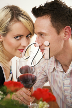 Young couple romantic dinner: clinking glasses with red wine