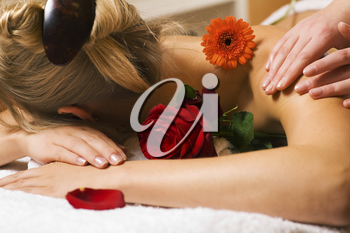 Beautiful blonde girl getting a massage in a spa setting and feeling visibly good about it
