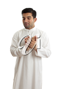 A worried,troubled, stressed or sad ethnic middle eastern or arab man in traditional  white robe.  White background.