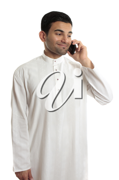 Ethnic mixed race middle eastern man in traditional dishdasha, kurta, thobe, robe, with silver buttons inlaid with rubies is chatting on a mobile phone, cellphone.