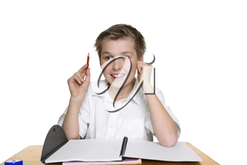 Happy school student sitting at desk with an idea or answer
