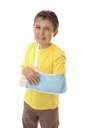 Injured young boy with sore arm in an arm sling