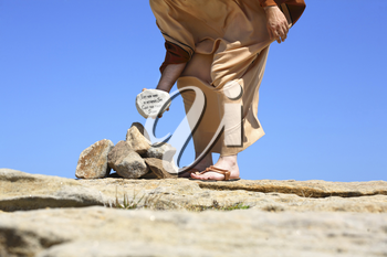 Man standing in the sun on sandy rocks holding a rock depicting ansswer by Jesus  from John Chapter 8. The pharsees were trying to enforce Leviticus 20: 10 however they overlooked Deuteronomy 1: 16, 1