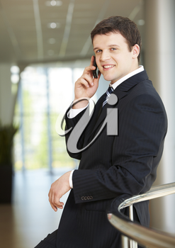 Photo of handsome employer speaking on the phone with potential business partner