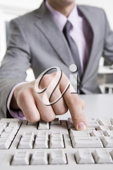 Close-up of businessman sitting at the table and typing a letter