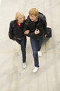 Image of couple walking down with their baggage and chatting