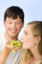 Image of young pretty girl eating grapes placed on man�s hand