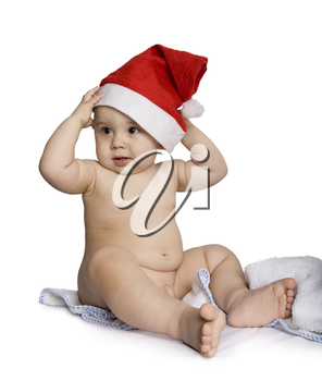 Photo of adorable toddler touching santa cap on his head and looking aside