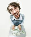 Fish-eye shot of happy young man holding several packs of dollars and smiling