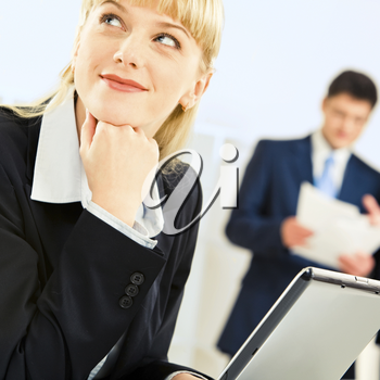 Portrait of confident blonde woman looking aside touching her chin with hand in working environment