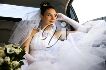 Portrait of young girl wearing white wedding gown sitting in car with her bouquet near by