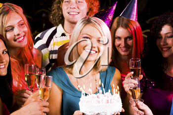 Portrait of joyful girl holding birthday cake surrounded by friends with flutes of champagne