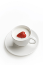 Shot of white cup full of milk with ripe strawberry inside
