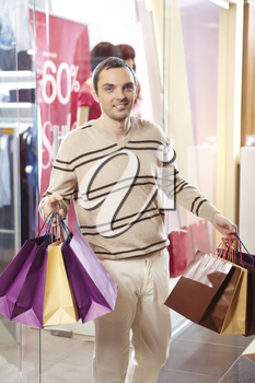 Happy man with bags looking at camera with smile in the mall