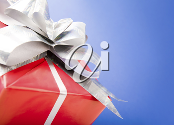 Macro image of silver knot on red giftbox isolated over blue background