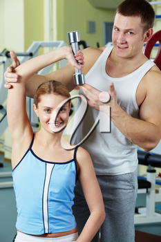 Portrait of sporty woman doing exercise with dumbbell and her trainer near by