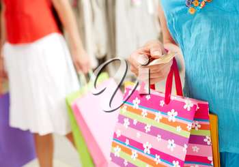 Image with focus on woman�s hand giving plastic card in the mall