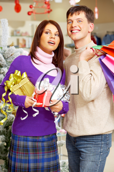 Portrait of happy young couple with Christmas gifts looking somewhere in shopping center