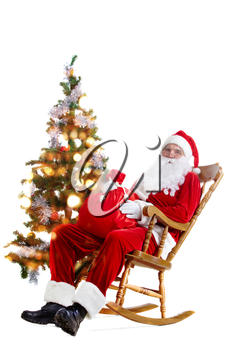Santa sitting in the armchair at the Christmas tree and holding a sack isolated on white