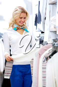 Portrait of pretty woman choosing new sweater in clothing department