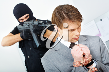 Portrait of confused businessman with bound hands being chased by gangster pointing gun at him