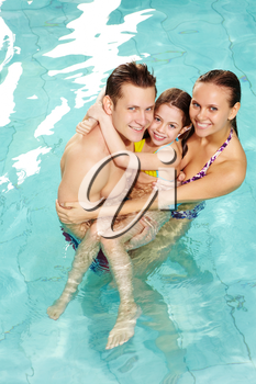 Photo of happy family of parents and cute daughter in swimming pool