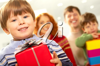 Portrait of smiling boy with gift looking at camera on background of family