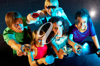 Portrait of smart young people toasting in the nightclub
