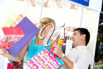 Joyful man and woman with bags looking at each other in the department store