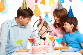 Portrait of happy boy having his birthday party with parents and elder brother near by