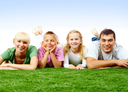 Portrait of happy family lying on green lawn and looking at camera