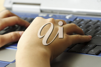 A working businesswoman with hands typing on her laptop