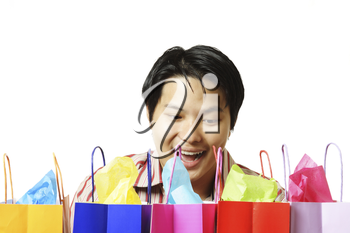 An isolated shot of a surprised young man with shopping bags