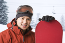 A shot of an asian snowboarder in a ski resort