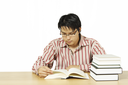 An isolated shot of a young man reading books