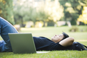 An asian college student lying down on the grass
