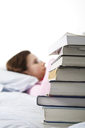 A caucasian college student reading and studying on her bed, focus on the textbooks