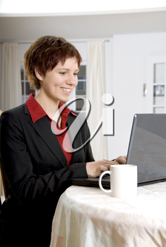 woman in a black suit working on her laptop