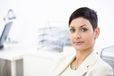 Portrait of businesswoman at office, smiling.