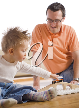 Father and little kid playing together with toy train in living room.