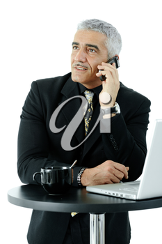 Mature businessman standing at coffee table, talking on mobile phone. Isolated on whte.