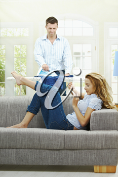 Relaxed young woman sitting on couch filing her nails, man ironing in the background. Selective focus on woman.